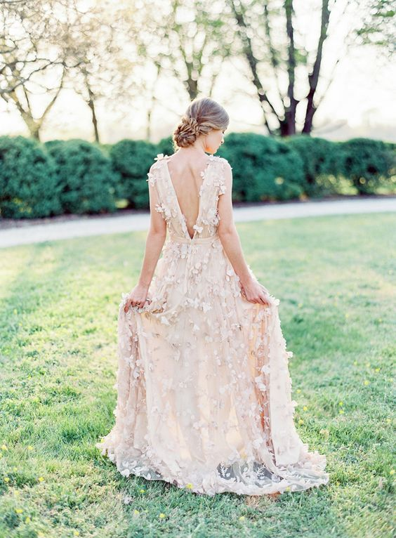 a blush A-line wedding dress with a low bakc and a train, with floral appliques is very refined