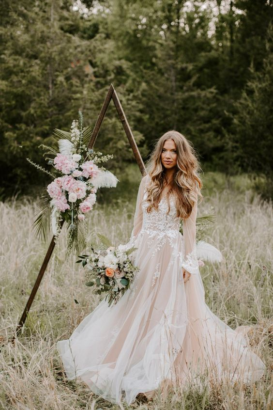 a blush A-line wedding dress with long sleeves and a V-neckline plus white lace