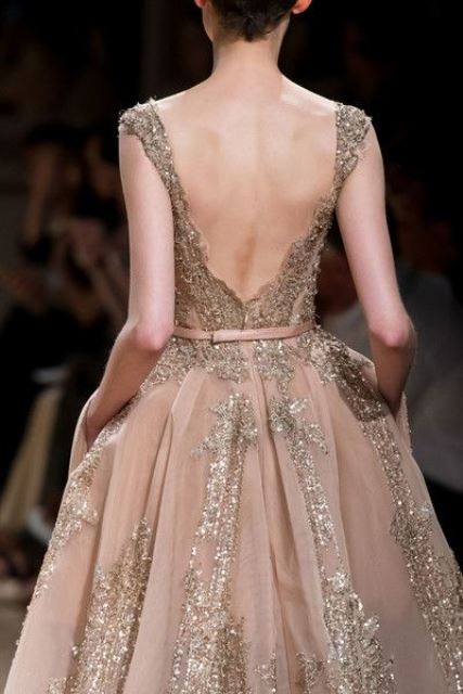 a blush princess-style wedding dress with gold embellishments and a sash is a very refined and beautiful idea with a low back