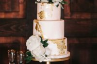a blush wedding cake with gold leaf decor and fresh white blooms and foliage for a vintage and elegant feel