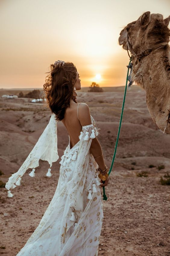 a boho A-line wedding dress in white, with gold lace detailing, tassels, a low back and a cold shoulder is very refined and chic