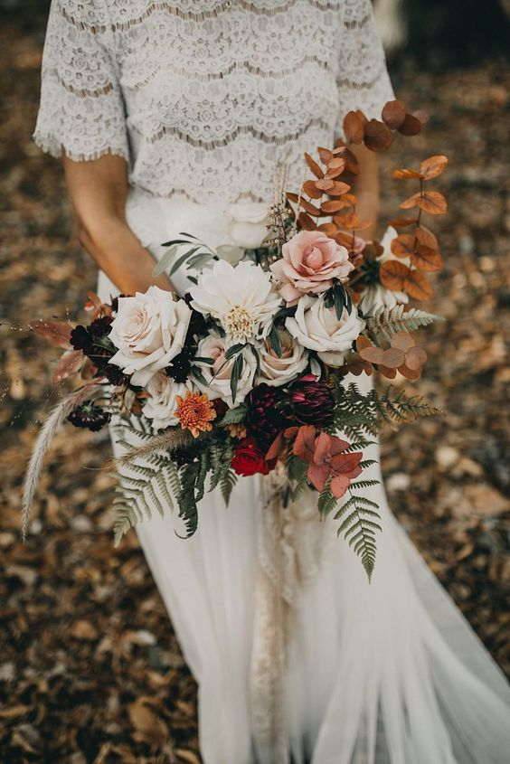 a boho fall wedding bouquet of white, pink and red blooms, deep purple ones, dried leaves and green ones