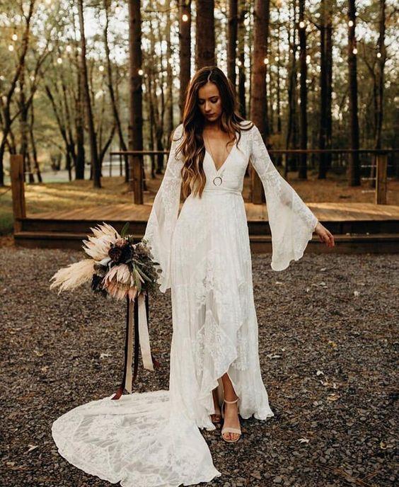 a boho lace A-line wedding dress with a deep V-neckline, bell sleeves and a train for a boho bride