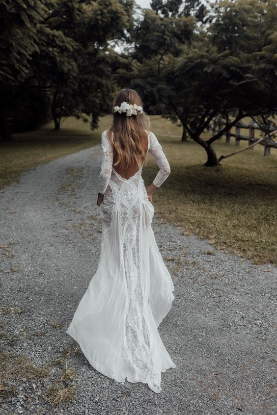a boho lace A-line wedding dress with long sleeves and a train, a low back is a very chic and cool idea