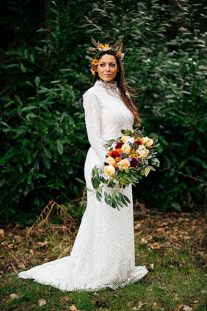 a boho lace fitting wedding dress, a high neckline, a train and a bold floral crown