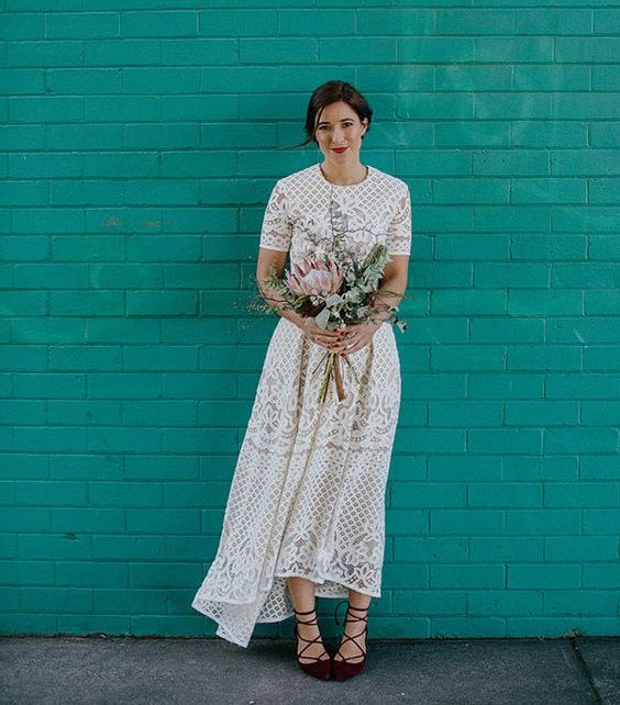 a boho lace high low wedding dress with a high neckline, short sleeves and burgundy lace up heels