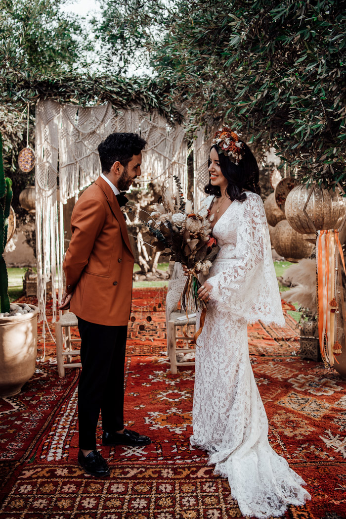 a boho lace sheath wedding dress with a V-neckline, bell sleeves and a train plus a floral crown for a boho wedding