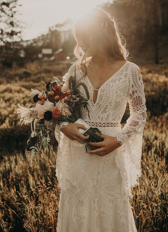 a boho lace wedding dress with a V neckline, a cutut, bell sleeves and a fittign silhouette