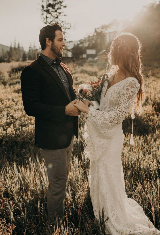 a boho lace wedding dress with bell sleeves, a V-neckline, tassels and a train for a boho backyard bride