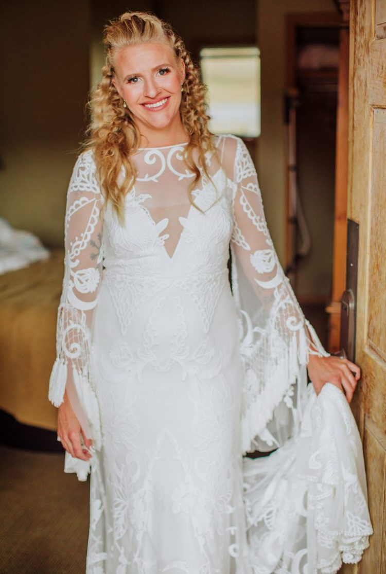 a boho lace wedding dress with bell sleeves with tassels and an illusion neckline plus a train and braided hair for a boho bride