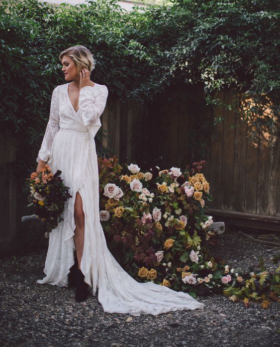 a boho lace wrap wedding dress with long sleeves and a slit plus a train and black boots for a touch of rock