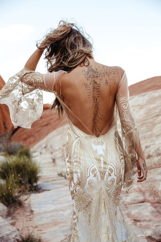 a boho mermaid wedding dress in white with gold lace detailing, a low back, bell sleeves and a train is chic