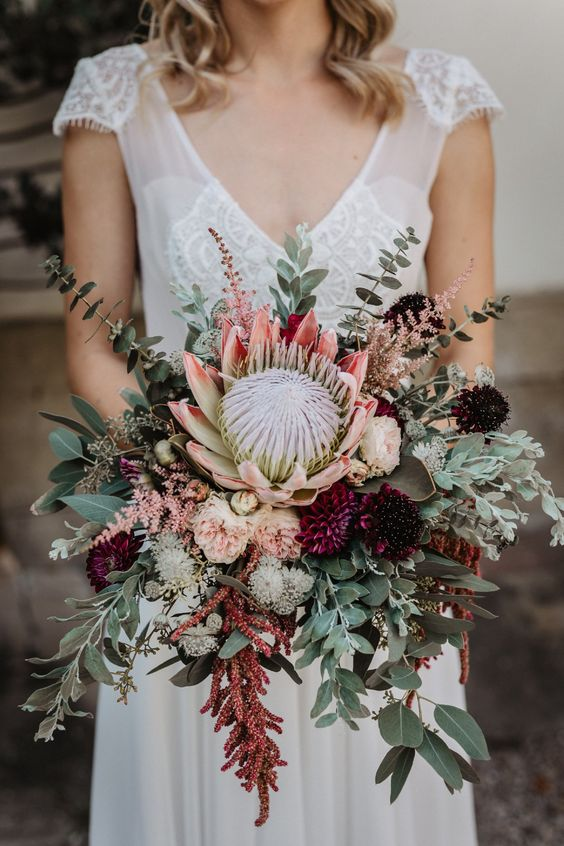 a boho summer wedding bouquet of greenery, blush and purple blooms, a giant king protea and eucalyptus