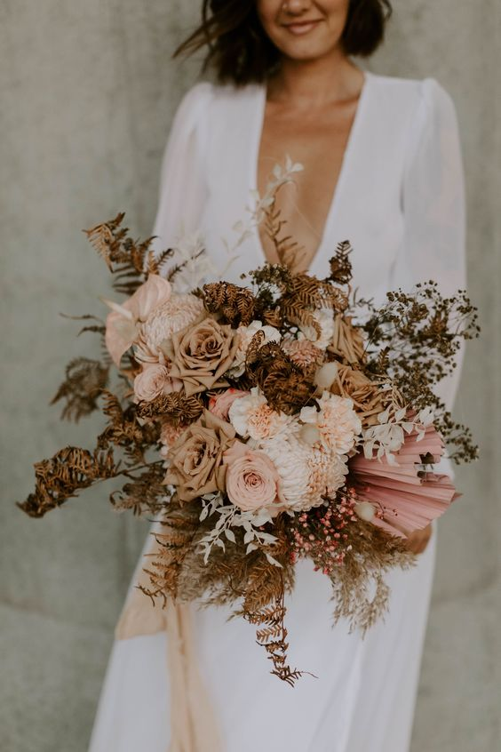 a boho wedding bouquet of blush and coffee colored blooms, dried leaves and grasses for a fall bride