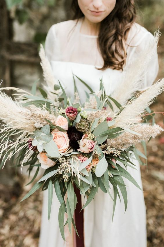 a boho wedding bouquet of blush and deep purple blooms, greenery and pampas grass is awesome