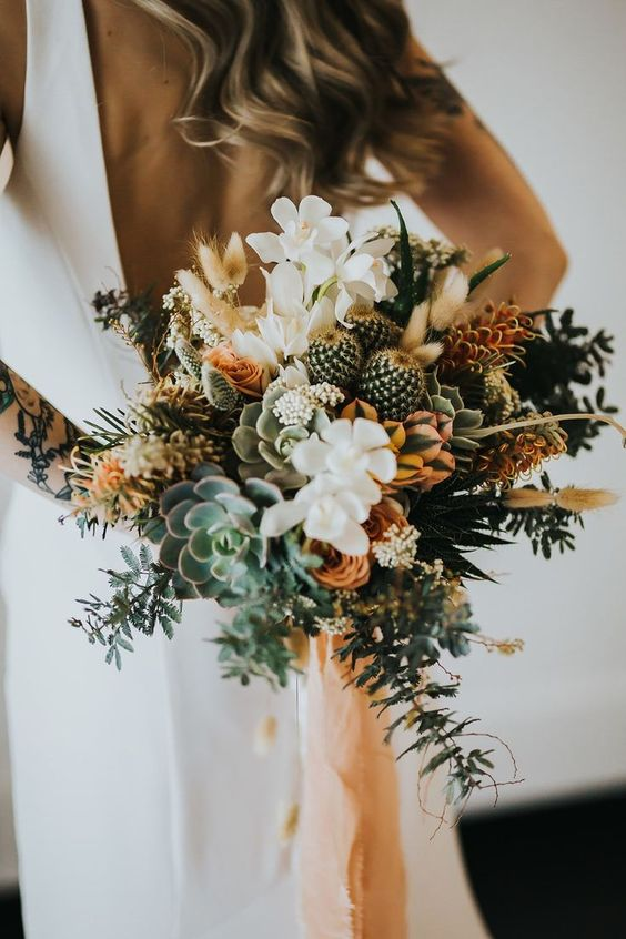 a boho wedding bouquet of succulents, cacti, white and rust blooms, greenery for a summer or tropical boho wedding