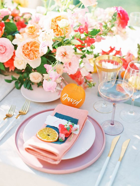 a bold and cheerful tropical wedding tablescape with bright blooms, pink plates and napkins, gold rim glasses and cutlery