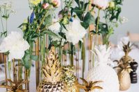 a bold and fun wedding centerpiece of clusters of blooms in various colors and mismatching gold and white pineapples