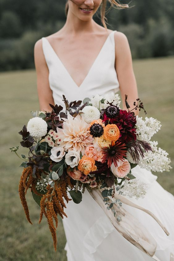 a bold fall boho wedding bouquet in blush, marigold, burgundy, white, with dark and neutral foliage