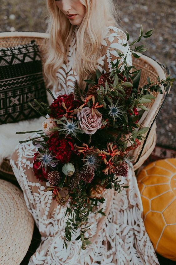 a bold fall boho wedding bouquet of red, dusty pink, deep purple blooms, thistles, greenery and cascading elements