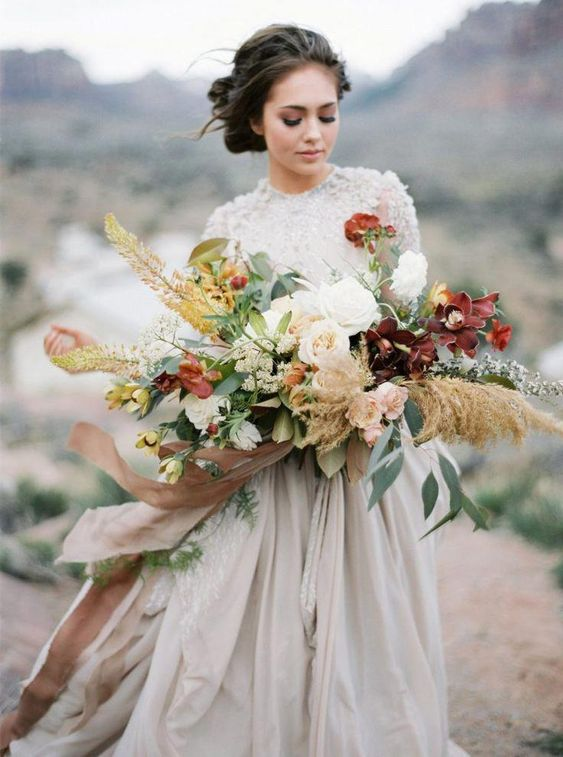 a bold fall wedding bouquet with burgundy and white blooms, greenery and pampas grass plus long ribbons