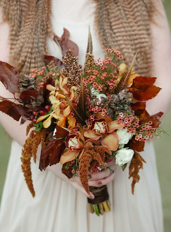 a bold fall woodland wedding bouquet of rust and gold blooms, feathers, bold fall leaves, berries and grasses is cool