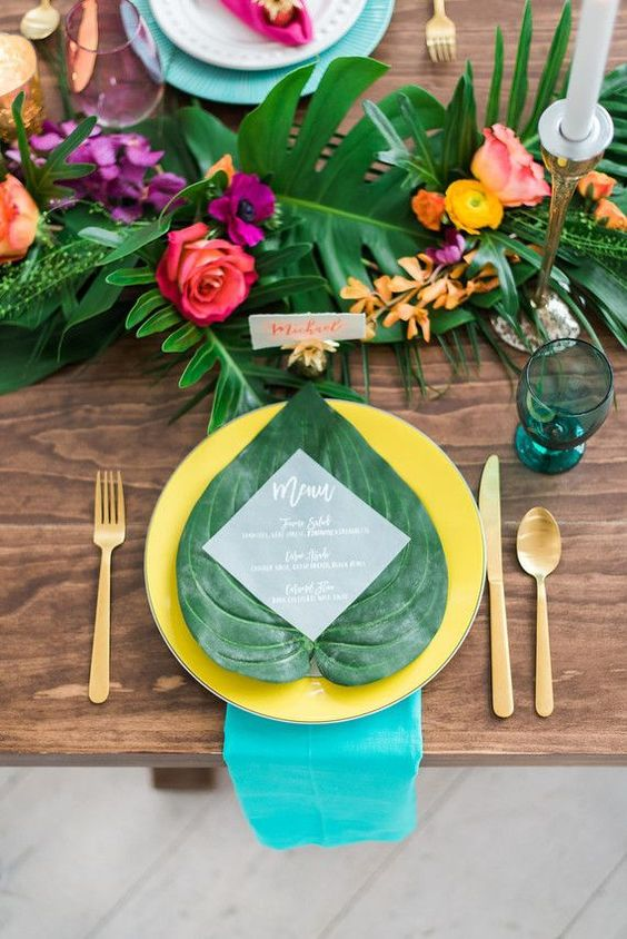a bold tropical wedding table with a greenery and bright bloom runner, turquoise napkins and yellow plates