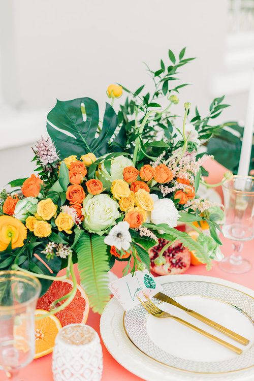 a bold tropical wedding table with a pink tablecloth, bright blooms, greenery and tropical leaves and candles