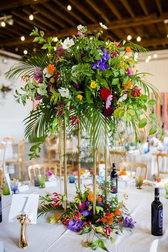 a bold tropical wedding table with a super colorful floral centerpiece on a tall stand, gilded figurines and colored glasses