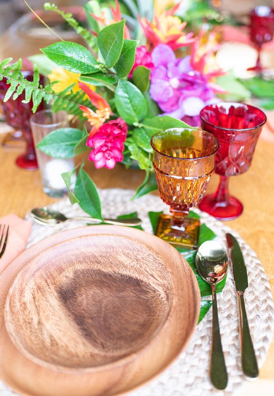 a bold tropical wedding table with bright blooms, greenery, colored glasses, wooden plates and gold cutlery