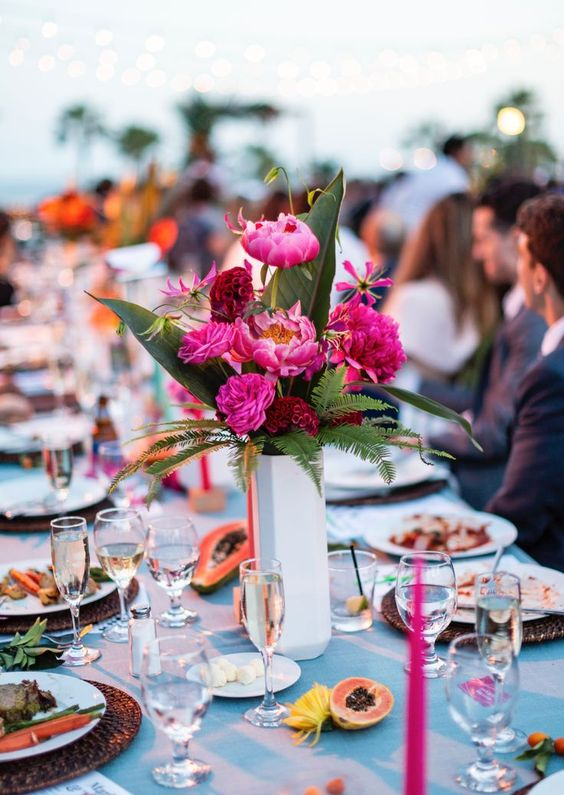 a bold tropical wedding table with woven chargers, bright blooms and greenery and fruits is bright classics