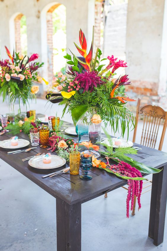 a bold tropical wedding tablescape with colored glasses, a greenery runner and bold floral arrangements