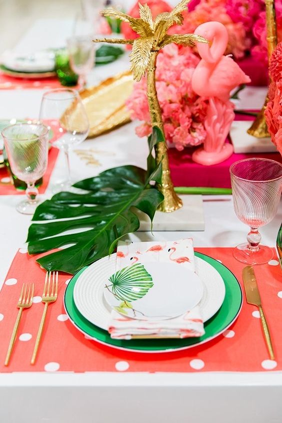 a bold tropical wedding tablescape with pink placemats, green chargers and tropical leaves, pink blooms and gilded palm trees