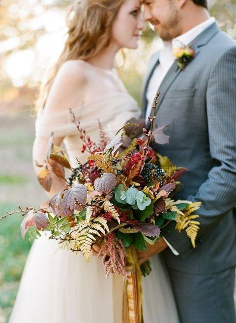 a bold woodland wedding bouquet with greenery, bold fall leaves, privet berries and long colorful ribbons