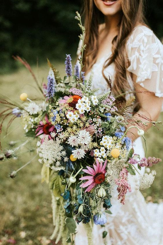 a bright boho summer wedding bouquet of white, pink, yellow, orange blooms, greenery and textural touches