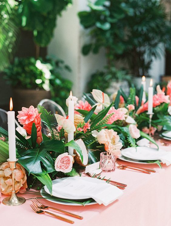 a bright pink wedding tablescape with pink blooms, glasses, a tablecloth, candles and tropical leaves