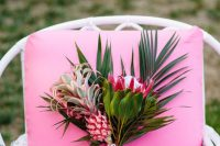 a bright tropical wedding bouquet with tropical blooms, leaves and a mini pink pineapple for a tropical bride