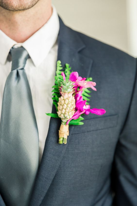 a bright tropical wedding boutonniere with hot pink blooms, greenery and a mini pineapple is a lovely idea