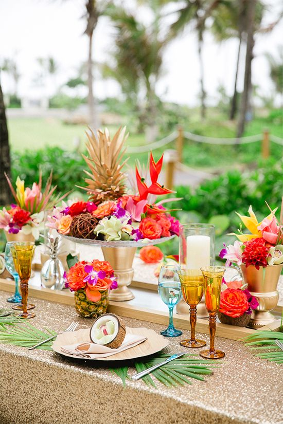 a bright tropical wedding table with a gold sequin runner, colorful glasses, bold blooms on a stand and some leaves and fruit