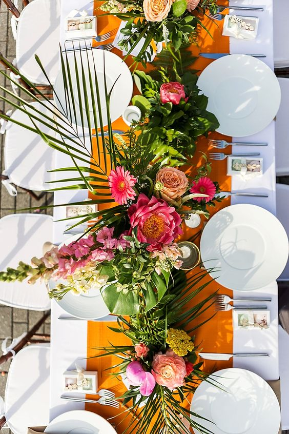 a bright tropical wedding table with a mustard runner, bold blooms, greenery and leaves, white porcelain and candles