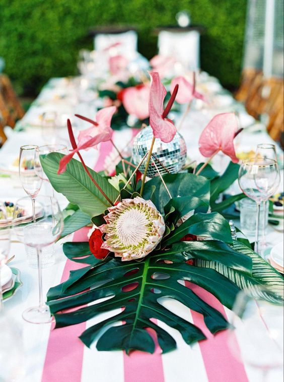 a bright tropical wedding table with a striped pink runner, bold blooms and tropical leaves and a disco ball