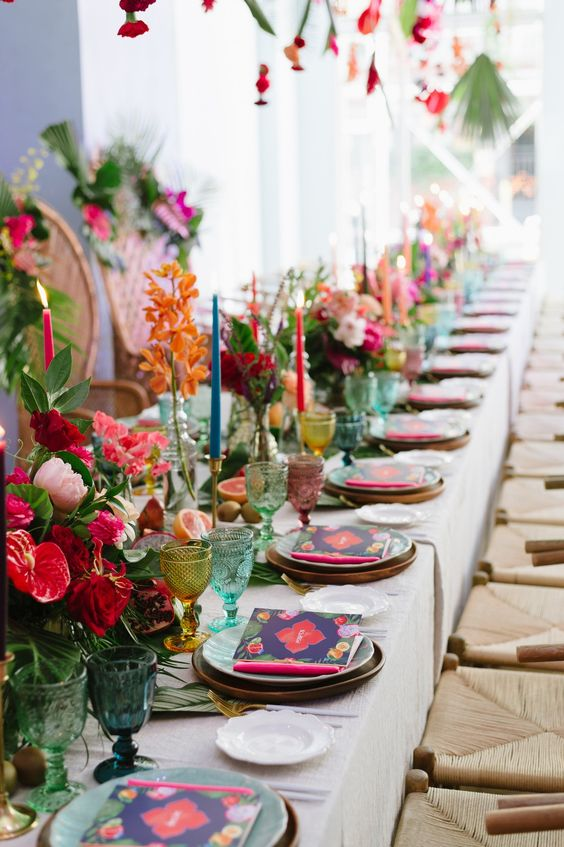 a bright tropical wedding table with bold blooms, greenery, colored glasses and bold stationery and candles