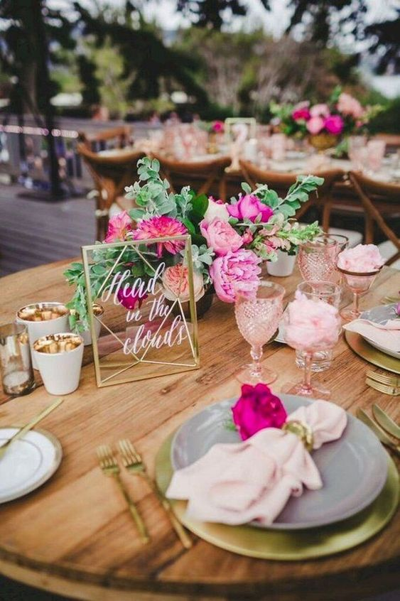 a bright tropical wedding table with bold blooms, pink napkins and glasses, candle lanterns and candle holders gilded inside