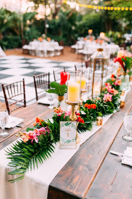 a bright tropical wedding tablescape with a neutral fabric and a greenery and bold floral runner, candles, neutral napkins and large tropical leaves