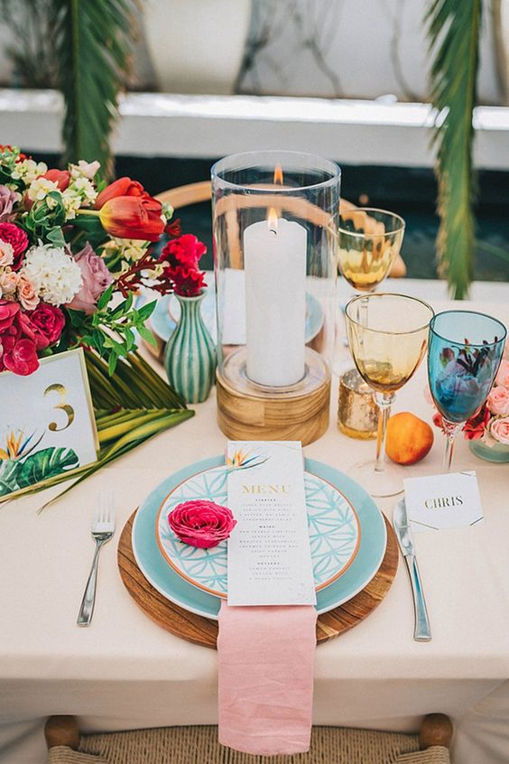 a bright tropical wedding tablescape with bold blooms, blue plates, pink linens and colored glasses