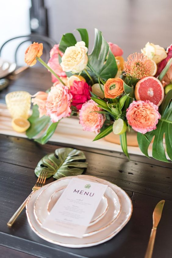 a bright tropical wedding tablescape with muted and bold blooms, tropical leaves, gold cutlery and a blush table runner