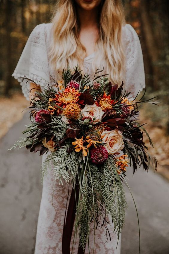 a bright wedding bouquet of orange, burgundy, pink and rust blooms, greenery and cascading elements