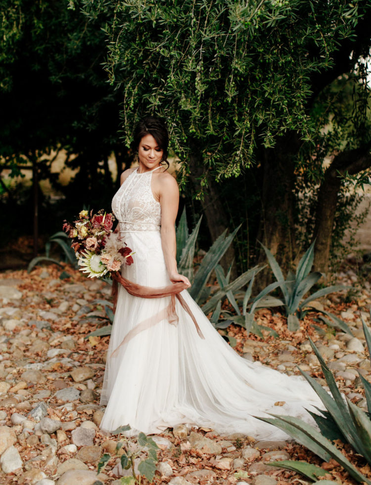 a chic A-line wedding dress with a lace bodice and a halter neckline plus a plain skirt with a train is adorable