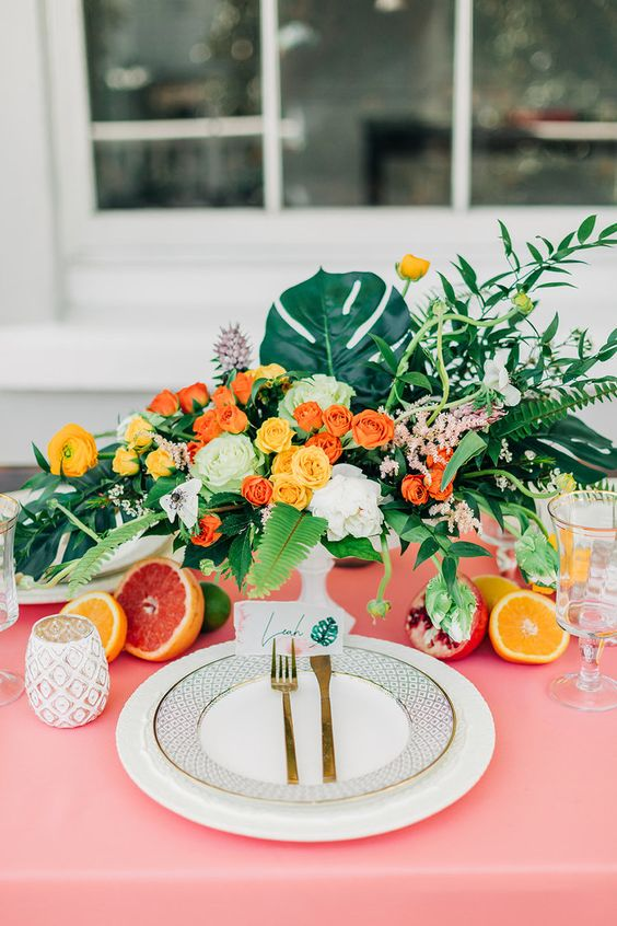 a chic and bold wedding tablescape with a pink tablecloth, bright blooms and greenery, citrus and gold cutlery