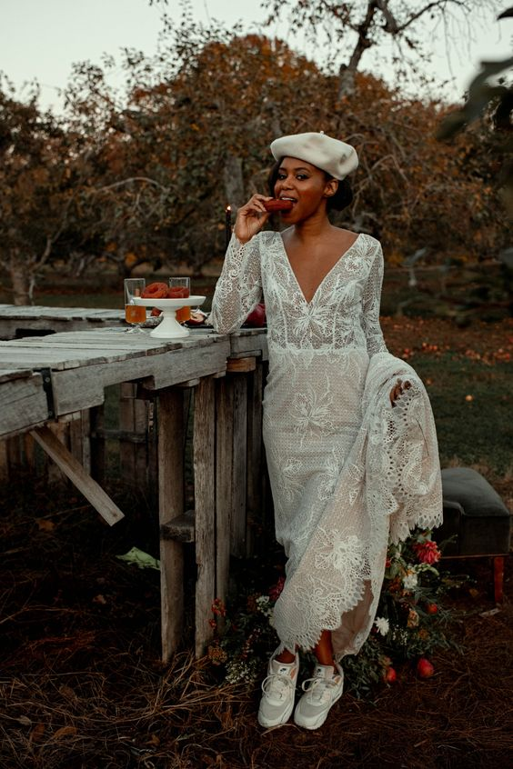 a chic boho lace A-line wedding dress with long sleeves, a V-neckline, grey trainers and a white beret for a wow look